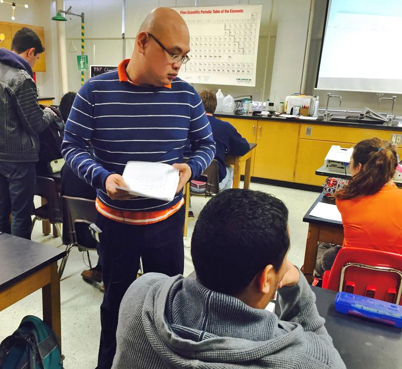 Rachmad Tjachyadi collects homework assignments from his AP chemistry students at W.T. White High School in Dallas ISD.