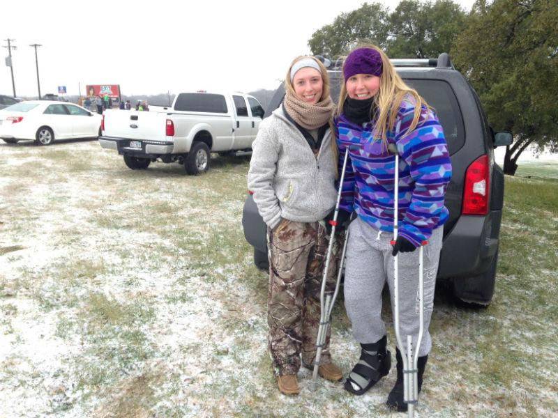 Taylor Foster and Stephanie Hall are first-year students at Tarleton State University in Stephenville. Despite her foot injury, Foster insists on sledding at a city park with the help of her friend.