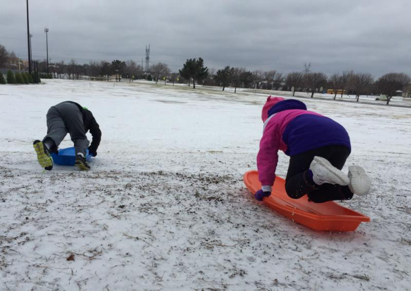 Monday's sleet makes for some fast-paced sledding. Members of the Gadd family test out their sleds in Plano.