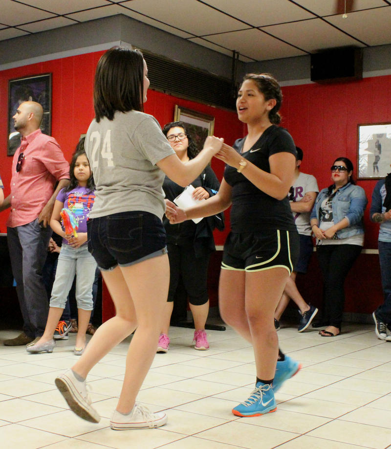 Liliana Casiano (right) dances with her friend.