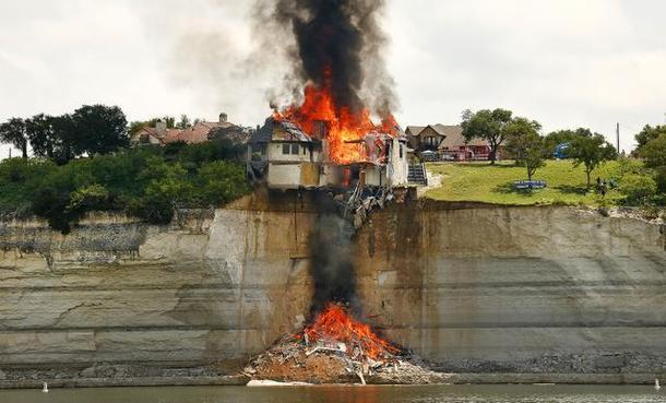 The house on a cliff over Lake Whitney was intentionally set on fire last summer.