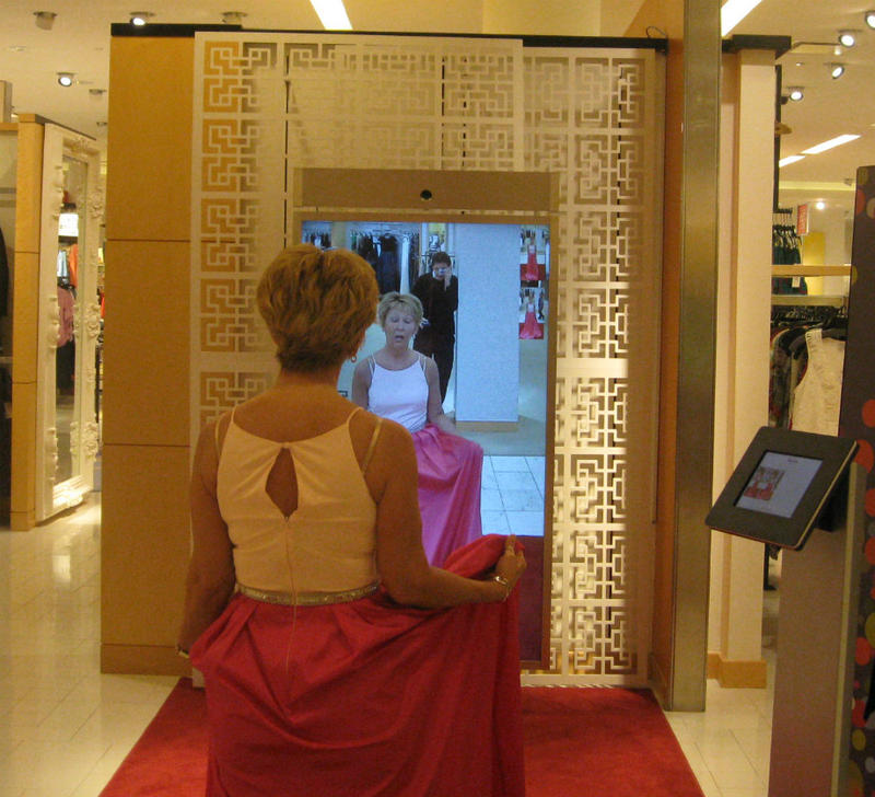 Neiman Marcus customer Laurie Schneider tries on a dress in front of the store's digital mirror. It records a video of her, so she can view the outfit at every angle and see others she's tried on side by side.