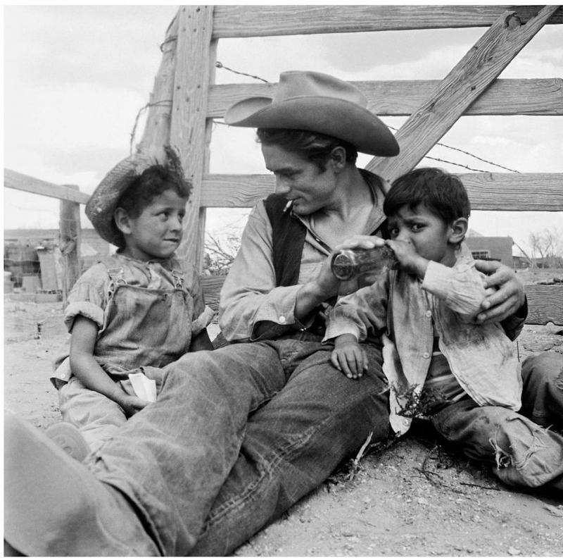 James Dean lounges on the set of 'Giant' in Marfa with two local kids who appear in the film.
