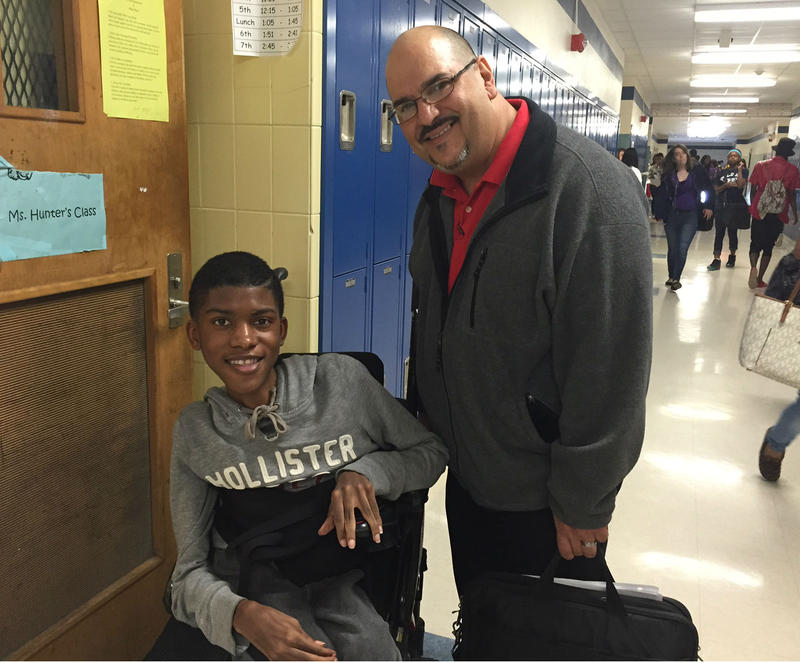 Chance Hawkins, a 10th grader at Fort Worth's Dunbar High School, is getting help this semester from an aide. Edgar Ortiz helps him take notes and adjusts him in his wheelchair when Chance gets tired.