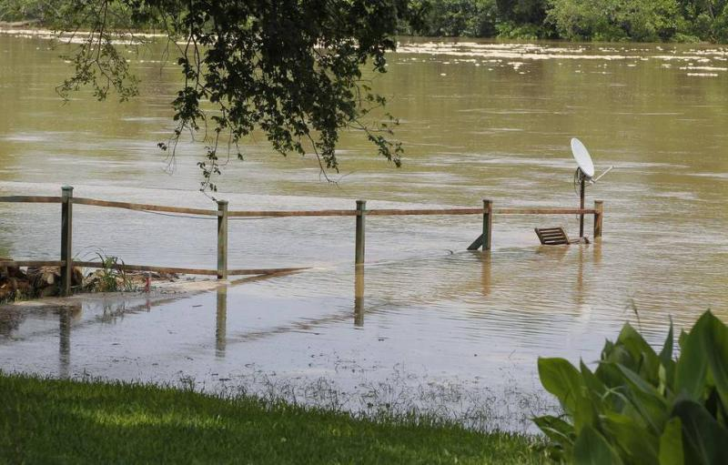 A fence is overtaken by the rising Brazos River in Horseshoe Bend on May 27.