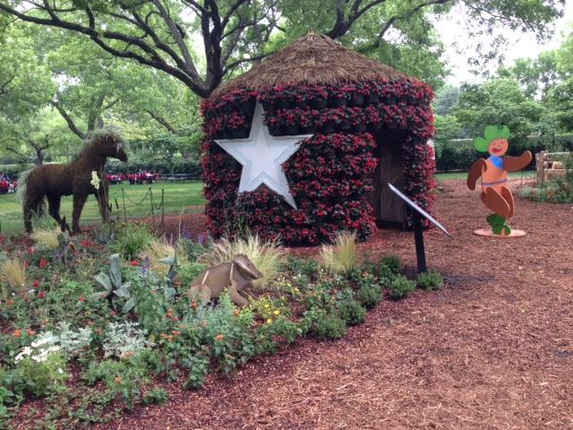 A flower house emblazoned with the Lone Star welcomes guests to this Texas-themed exhibit.