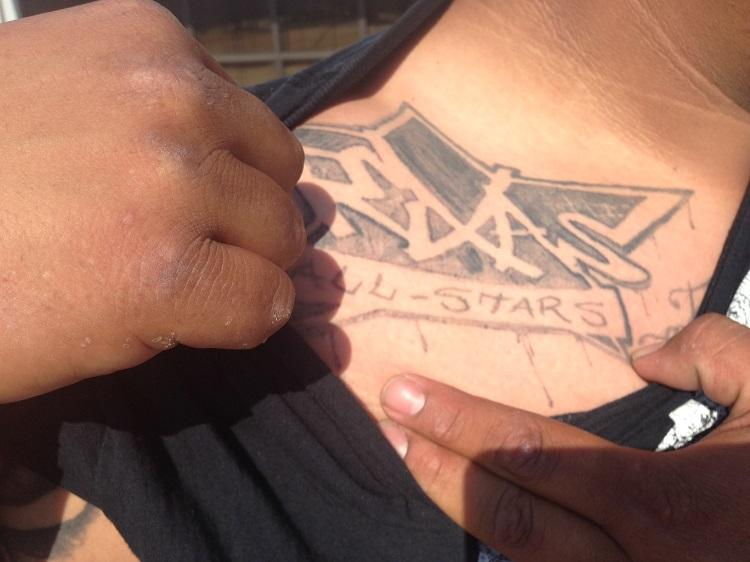 Juan has several tattoos, but none visible when he's dressed for work. This one can be considered a gang tattoo.