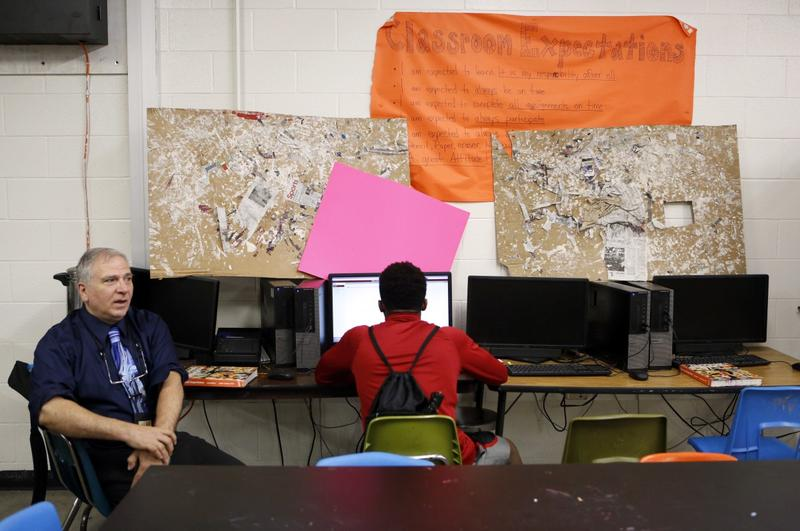 Mark Pierce, who runs DISD's homeless education program, helps a student with computer skills at the drop-in center at North Dallas High School.