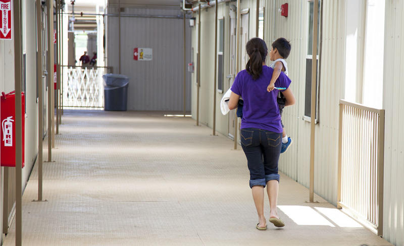 Residents walk through a common campus area at the South Texas Family Residential Center in Dilley.