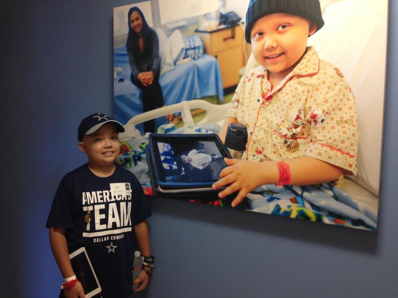 Jude Cobler stands next to a picture of him hanging on a wall at Children's Medical Center in Dallas. Jude's Acute Lymphoblastic Leukemia has relapsed.