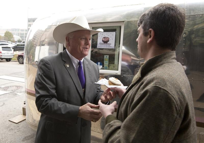 Texas Agriculture Commissioner Sid Miller gives away cupcakes at a press conference in January.