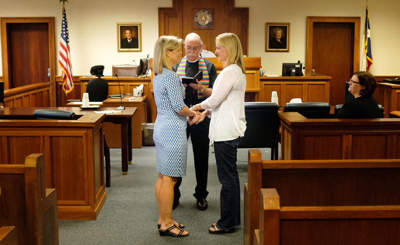 Diane Jones and Bryna Wortham stand with Rev. Richard Bates at their wedding ceremony at the Travis County Courthouse on Friday.