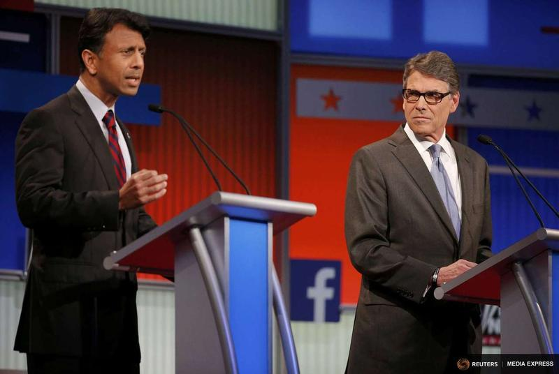 Bobby Jindal, Louisiana governor and Republican presidential candidate, answers a question as former Texas Gov. Rick Perry listens at a forum Thursday night in Cleveland.