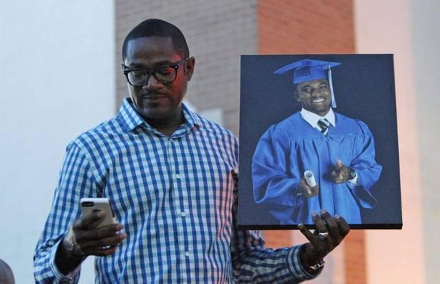 Dr. Ronnie W. Goines, senior pastor of Koinonia Christian Church, held a photo of Christian Taylor at a vigil.