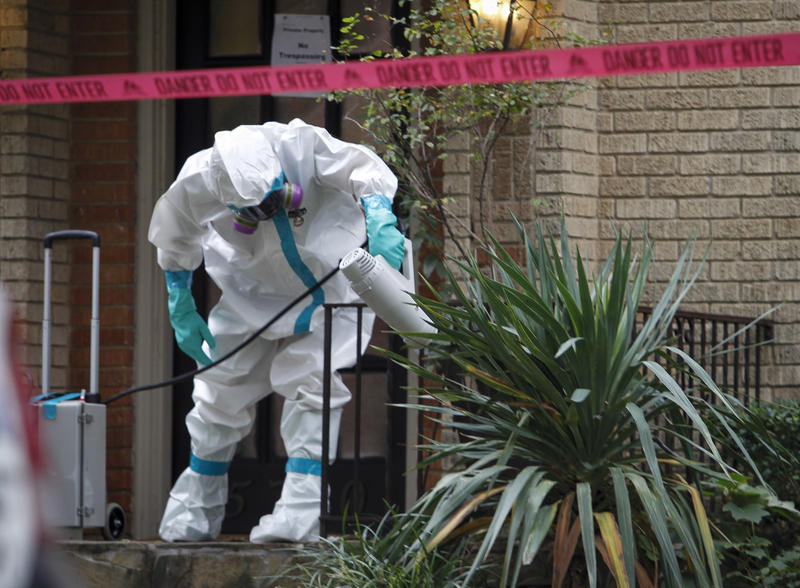 A worker with CG Environmental-Cleaning Guys sprays disinfectant outside the Marquita Street apartment building in Dallas  where a nurse infected with Ebola lives on Oct. 12, 2014.