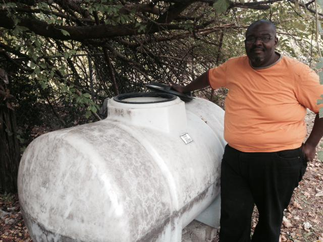 Pastor Eugene Keahey stands by the water tank at Mount Zion Missionary Baptist Church.