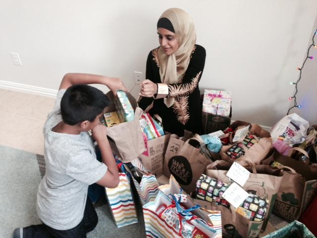 Farah Uddin and Salat Hussain sort through toy drive gifts in McKinney.