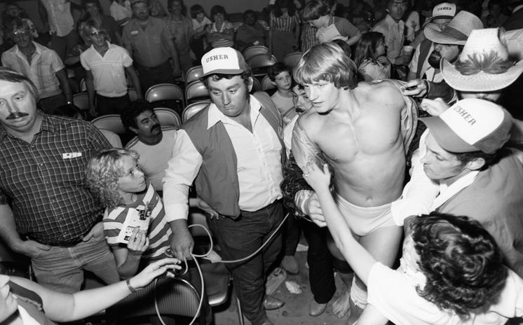 Ushers leading Kevin Von Erich to the ring through a crowd of exuberant fans.