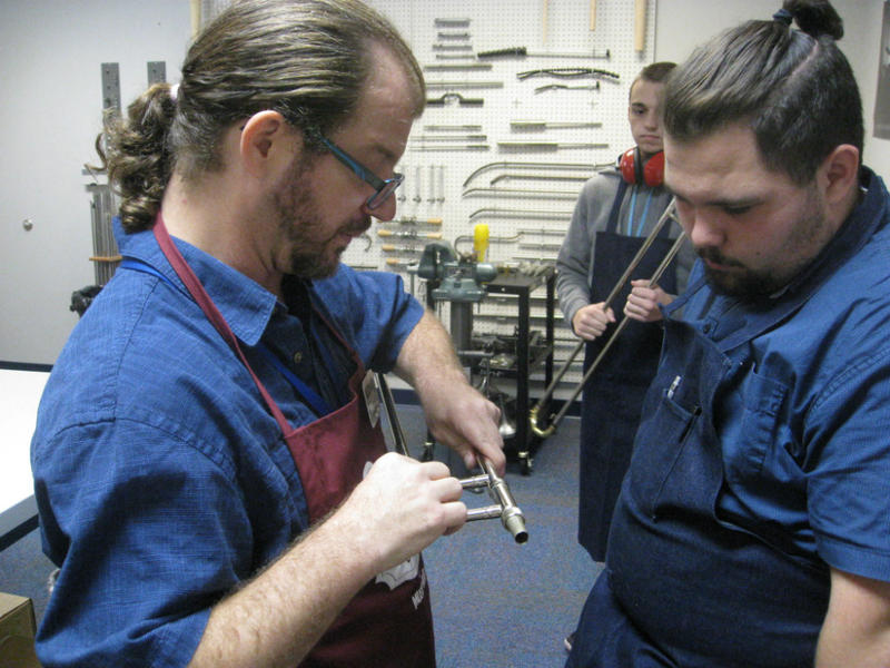 Instructor Joe Strohl, foreground, with trombone slide in hand, critiques instrument repair student Noah Patrick's work, as Patrick looks down.