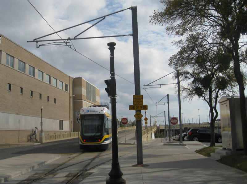 Dallas streetcar departs from the stop across from Union Station after the pantograph has detached from live wires overhead. Batteries charged, the car's rolling to Oak Cliff, no wires attached.