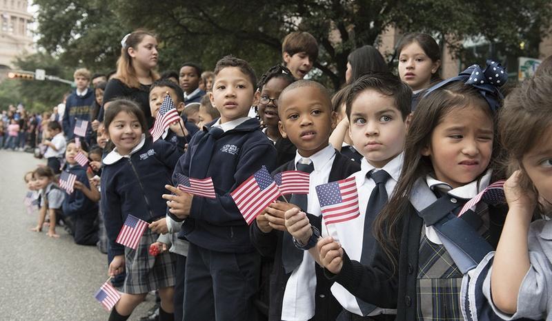 Schoolchildren watch the Veterans Day parade on Congress Avenue in Austin in November.