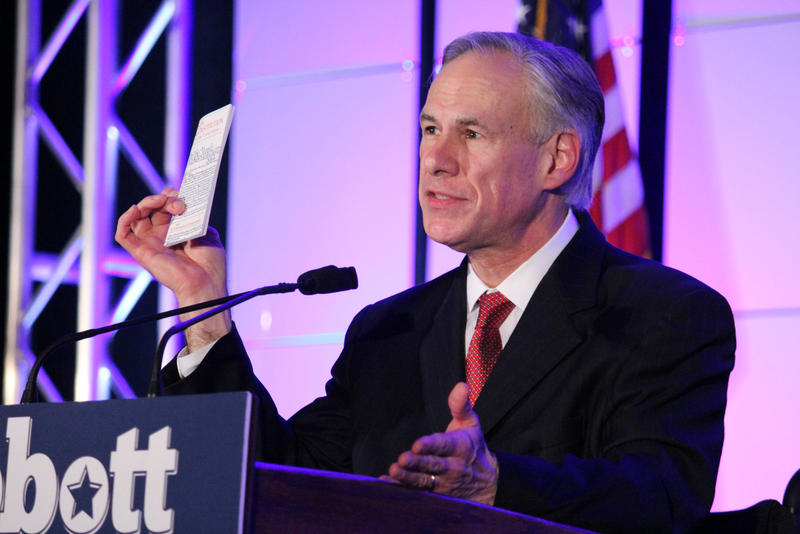 Gov. Greg Abbott, holding up a pocket US Constitution, spoke Saturday night in Fort Worth.