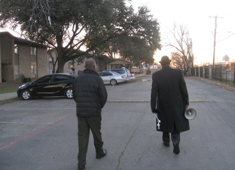 Interim Principal Alphonso Warfield, left, walks by apartments next to Pease Elementary. Assistant Principal Johnny Gassaway, megaphone in hand, joins him. They're trying to get students out of their homes and into school on time.