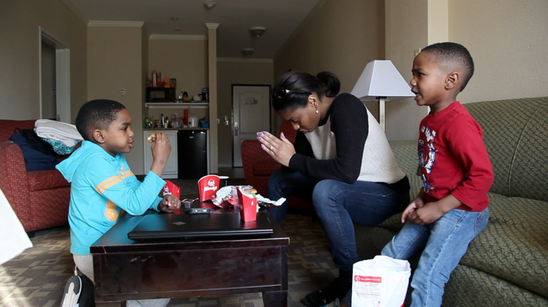 Jennifer Anderson and her two boys, Jayden and Jordan, pray before eating in their hotel room.
