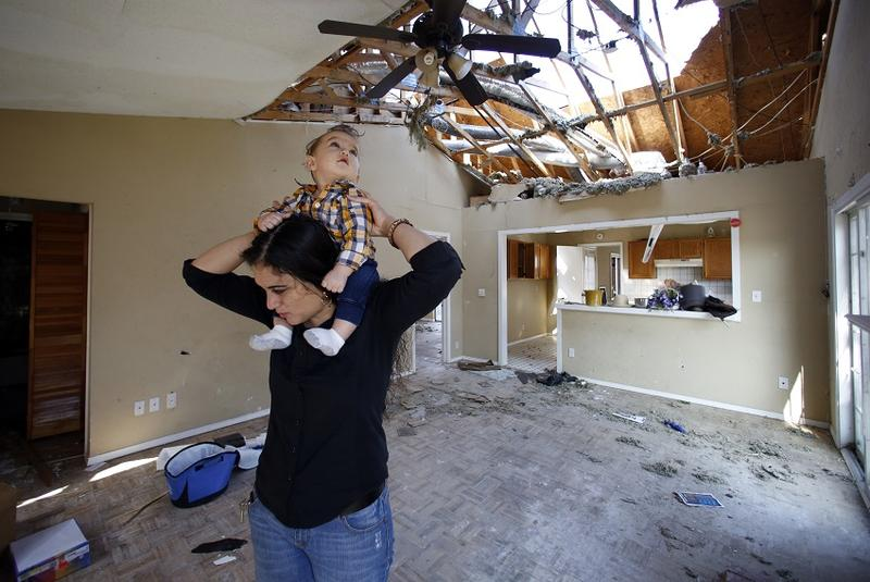 Lindsay Diaz checks out the damage at her Rowlett duplex. Her son Arian looks through the hole in the roof.