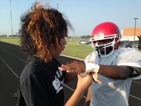 Phantasia learns to wrap the hand of a football player. The games are on Thursday nights.