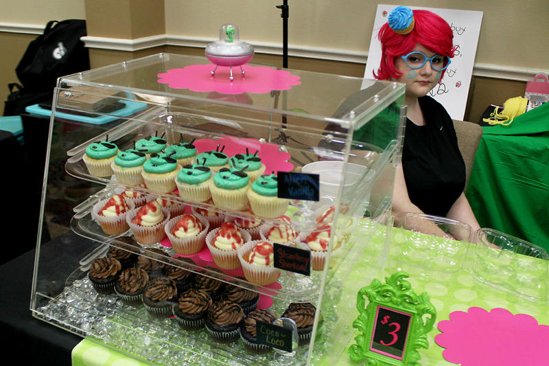Vendors at a conference in Aurora sold a range of UFO-related books and paraphernalia. Makayla Smith, 17, was selling alien-faced cupcakes.