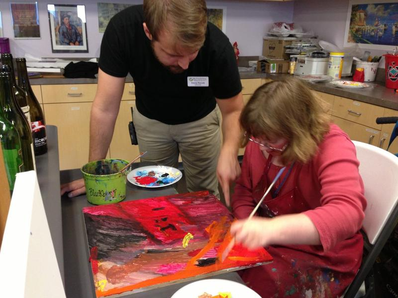 Instructor Casey Parrott, who oversees the Create program at My Possibilities, works with student Audrey on her rainbow painting.