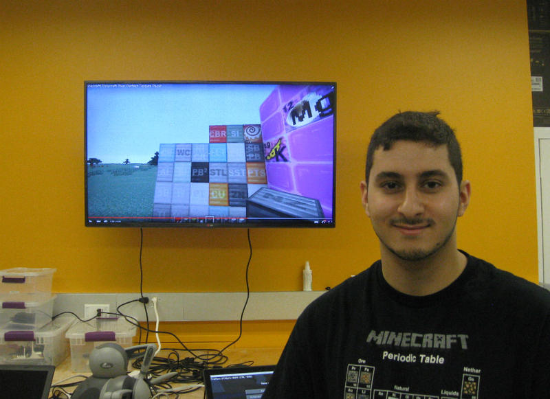 UT Dallas student Husam Wadi in front of one of his computer game creations that won him scholarship money at the school.