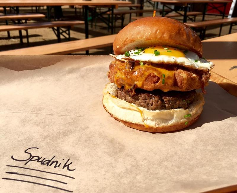 "One of Rodeo Goat's creations, ""The Spudnik,"" featuring topped with a smashed-fried potato wedge, bacon, cheddar cheese, a fried egg, and chive sour cream."