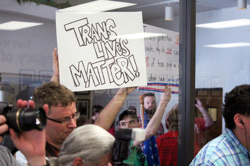 Advocates for the Fort Worth ISD transgender guidelines held signs up to the glass window where Lt. Gov. Dan Patrick told reporters FWISD head Kent Scribner should resign.
