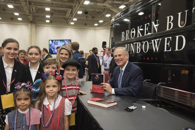 Gov. Greg Abbott poses with the Nelson family from Bedford after signing their book at the trade show of the Texas Republican Convention in May.