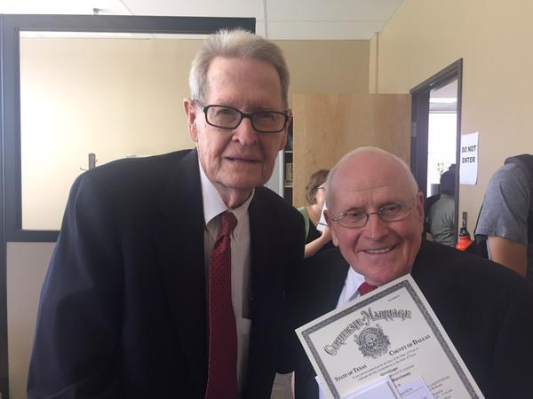 Jack Evans, left, and his husband George Harris holding their legal marriage certificate on June 26, 2015.
