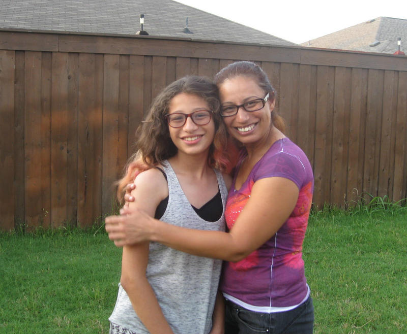 Roxy, a 13 year-old transgender girl getting a hug from  mom Angela Castro in their backyard.