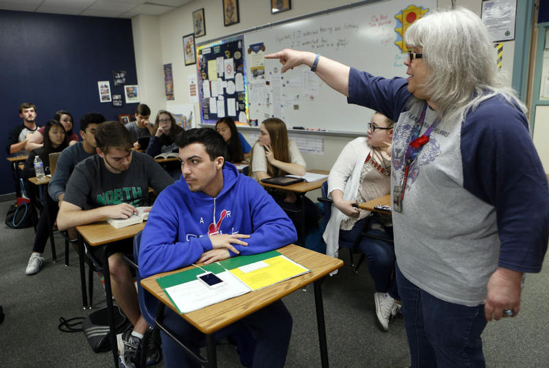Ricky Rijos, sitting, is in his 11th grade professional communications class as teacher Melody Barnhart points.