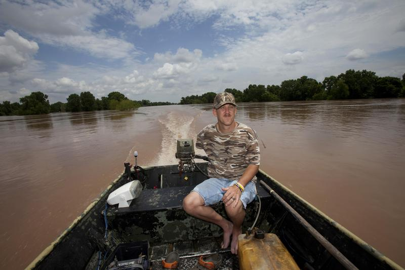 Jeff Harper drives his boat along the rain-swollen Brazos River near Houston on May 31.