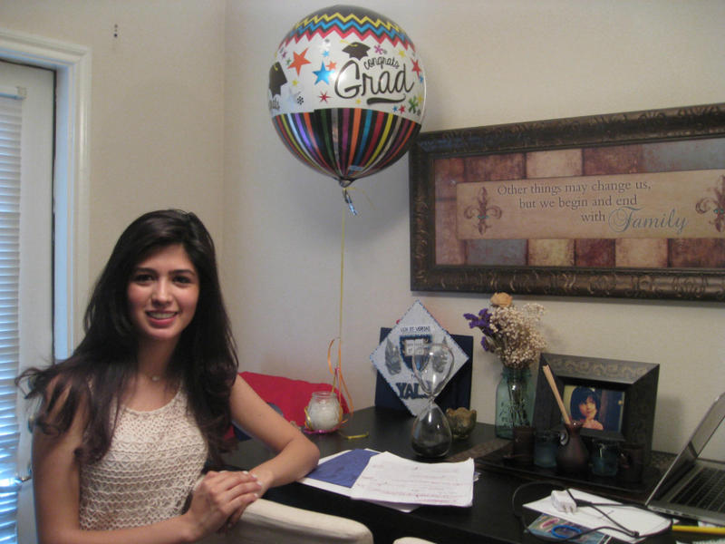 Larissa Martinez, standing by a celebratory balloon, her home-made Yale plaque,  her graduation speech, and a childhood photo of her.