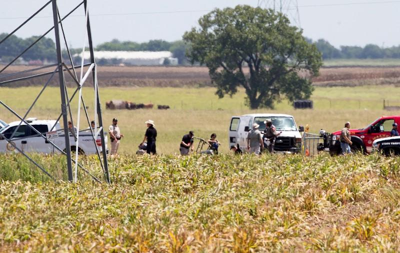 The partial frame of a hot air balloon is visible above a crop field as investigators comb the wreckage from the Saturday morning accident that left 16 people feared dead.