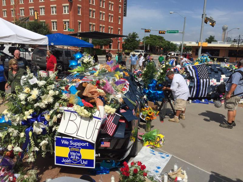 Residents show up at Dallas police headquarters to pay their respects to the officers who were shot in downtown.