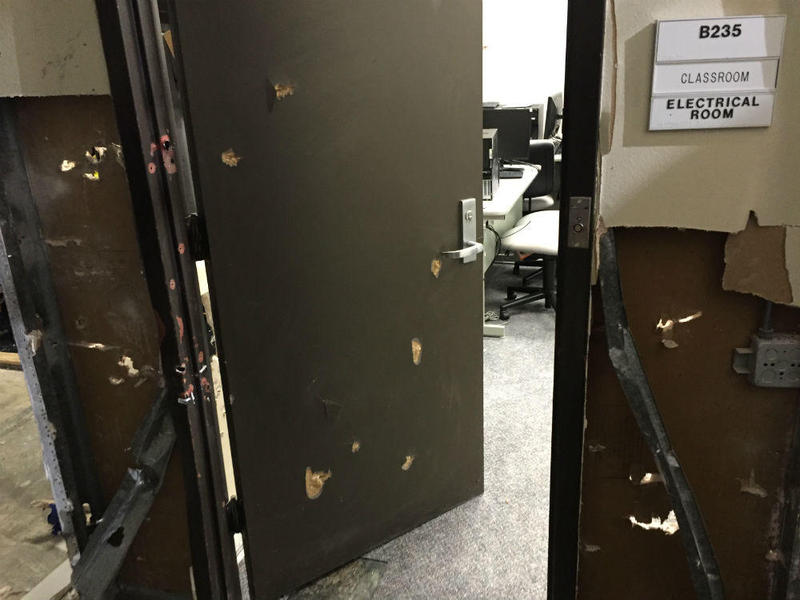 Bullet holes pockmark the entrance to this classroom.