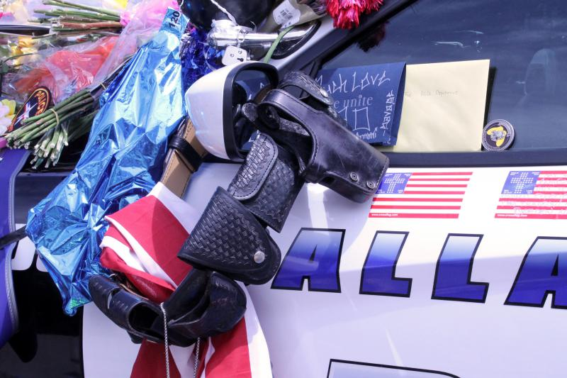 A police belt hangs over the sideview mirror of one of the cars.