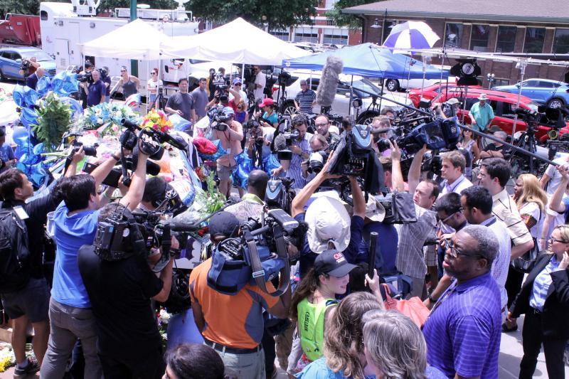 Reporters obscure Mayor Mike Rawlings as he kneels before the memorial.