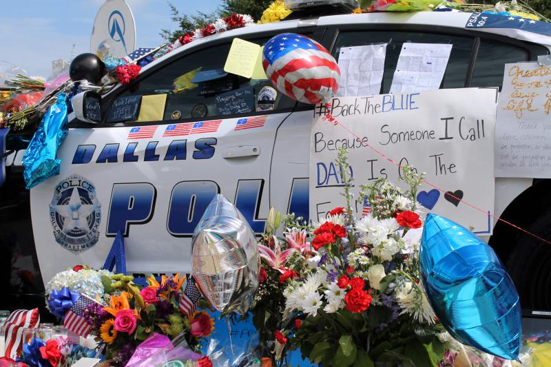 Two police cruisers outside Dallas police headquarters are covered in flowers, cards and stuffed animals in an impromptu memorial.