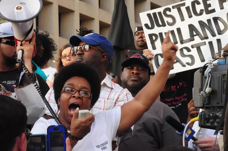 A woman yells into a microphone during a protest in downtown Dallas Thursday evening.