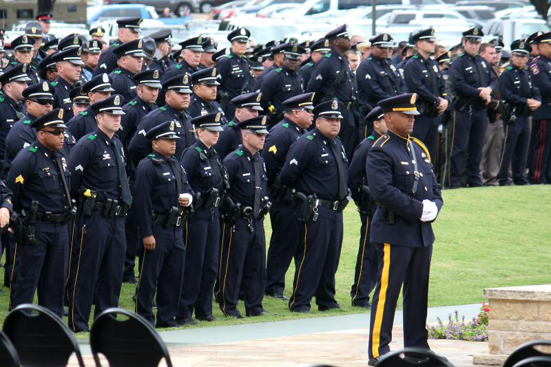Dallas police officers mark the passing of one of five fellow law enforcement officers killed when a gunman opened fire in downtown Dallas.