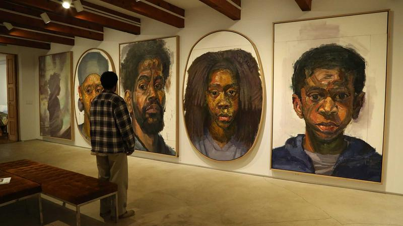 At Valley House Gallery in Dallas, Sedrick Huckaby stands in front of portraits of his children, his wife Letitia and himself.